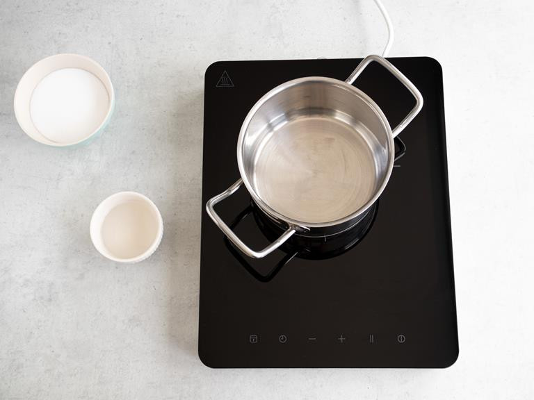 Garnek na kuchence indukcyjnej. Cukier i woda w osobnych miseczkach.