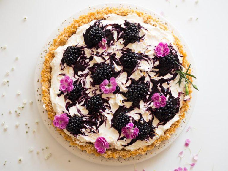 Tarta z białą czekoladą i jeżynami z fioletowymi kwiatami.