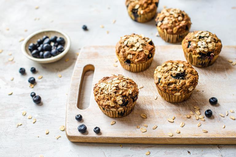 Wegańskie muffiny śniadaniowe z borówkami na drewnianej desce.