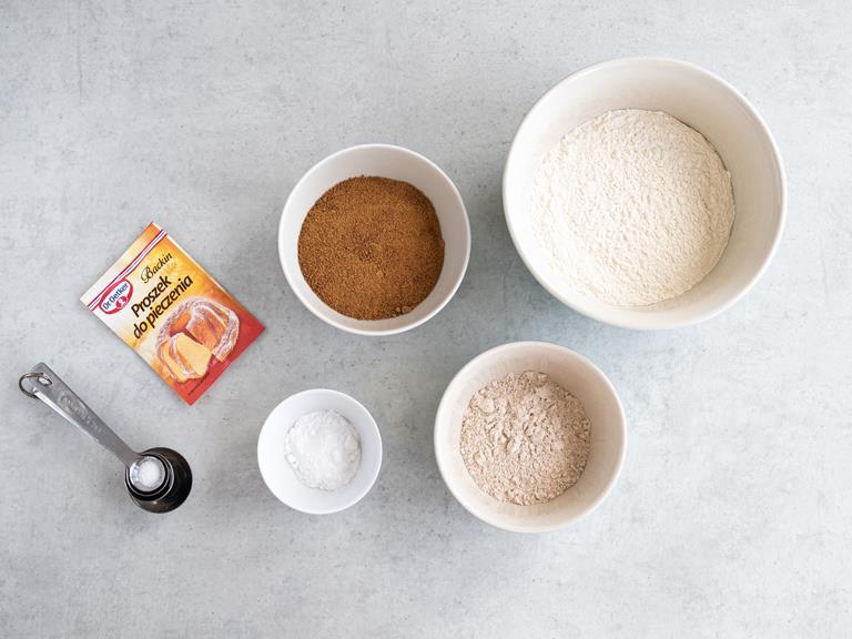 Składniki do ciasta: mąka pszenna, mąka pełnoziarnista, proszek do pieczenia, soda, sól i cukier kokosowy. Każdy składnik w osobnej miseczce.