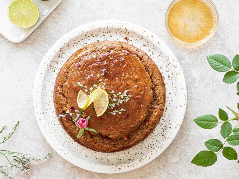 Ciasto z cukrem kokosowym i syropem grejfrutowym z różą, udekorowane plastrem limonki i świeżymi kwiatami.
