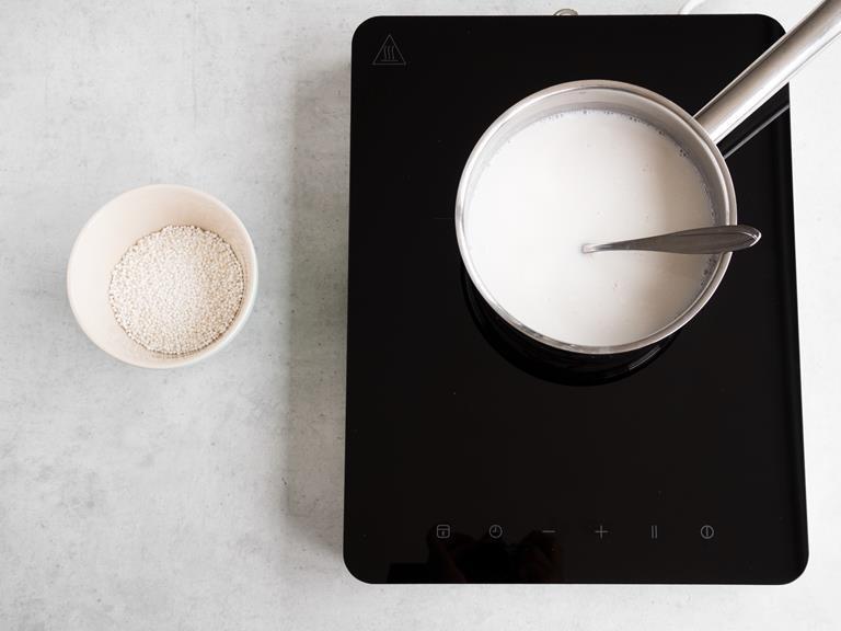 Kulki tapioki w miseczce.  W garnku na palniku mleko kokosowe z mlekiem migdałowym, sokiem z limonki i ksylitolem.