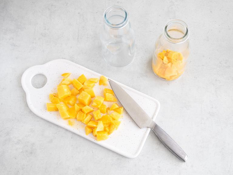 Pokrojone mango w kostkę na białej desce.