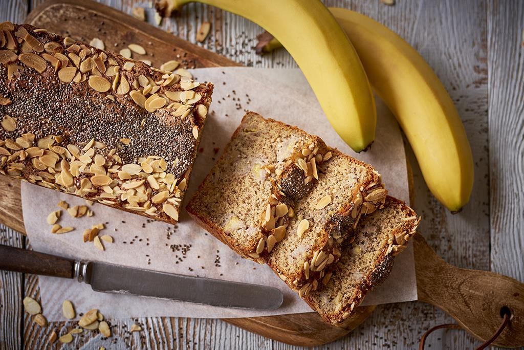 ciasto bananowo-migdałowe bez glutenu posypane nasionami chia i płatkami migdałów na desce