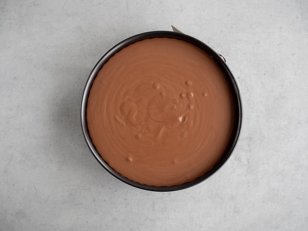 Masa czekoladowa przelana na biszkopty w tortownicy