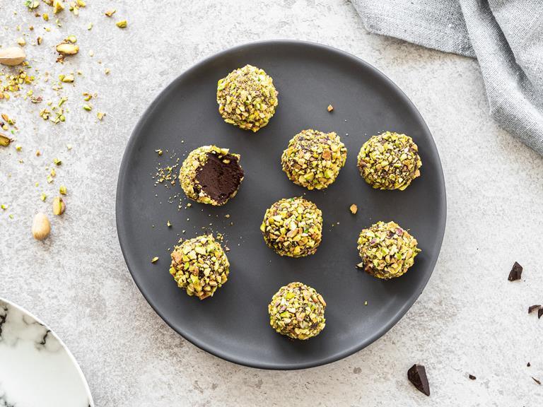 trufle czekoladowe z awokado obtoczone pokruszonymi pistacjami na ciemnym talerzyku.