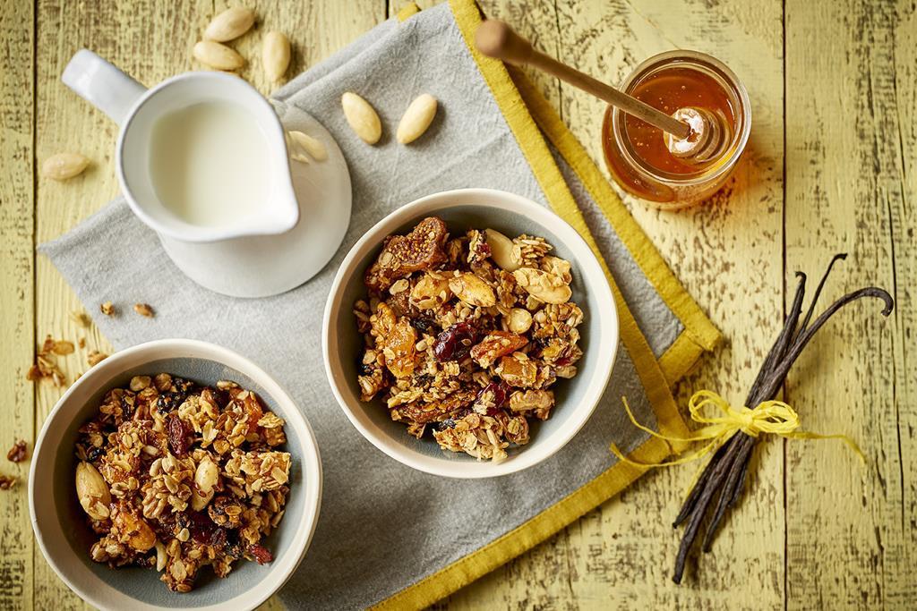 Bezglutenowa granola w miseczce z miodem i mlekiem