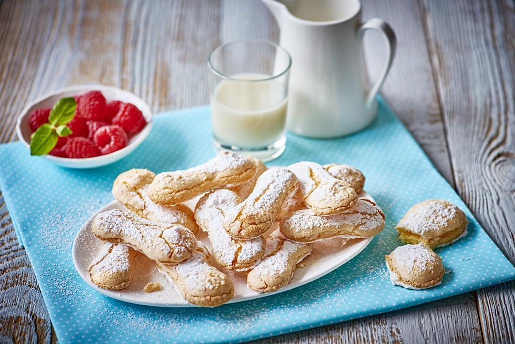 Podłużne biszkopty bez glutenu posypane cukrem pudrem położone na talerzyku