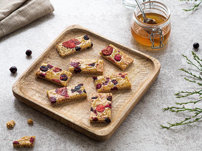 Sezamki z owocami liofilizowanymi na drewnianym talerzyku.