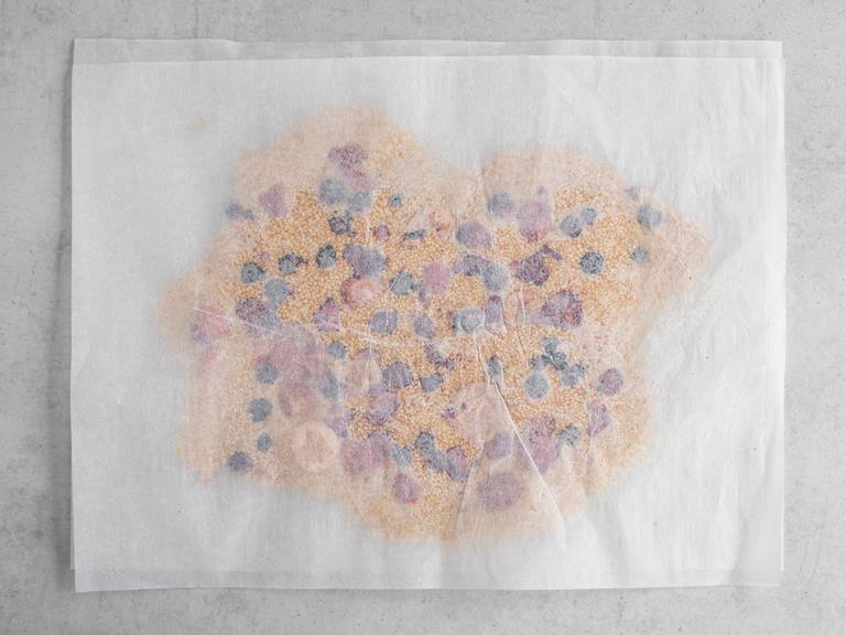 Masa sezamowa z owocami, przykryta papierem do pieczenia.