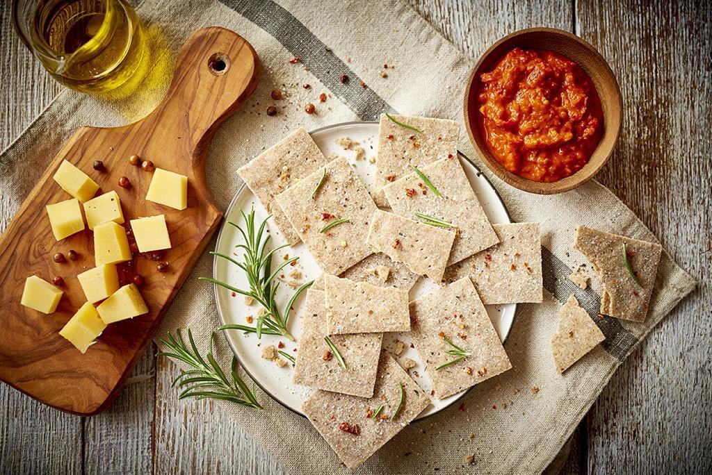 krakersy rozmarynowe bez glutenu pokrojone na kawałki, podane z serem