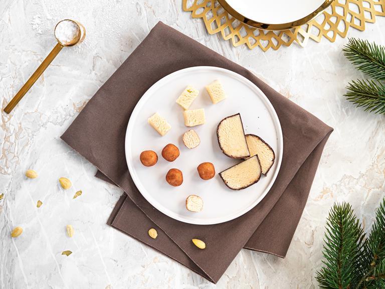 Marcepan w czekoladzie, kartofelki marcepanowe oraz pokrojony marcepan na talerzyku.