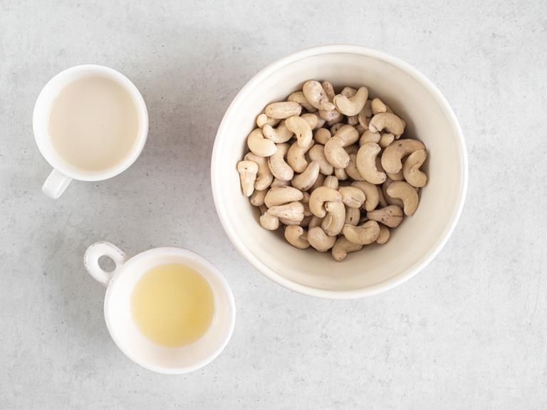 Orzechy nerkowca w misce. Obok mleko migdałowe i sok z cytryny.