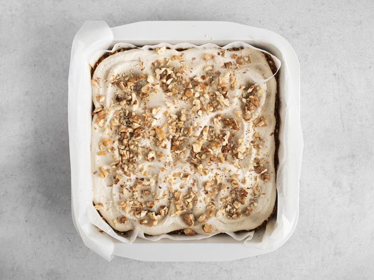 Ciasto marchewkowe posypane posiekanymi orzechami włoskimi.