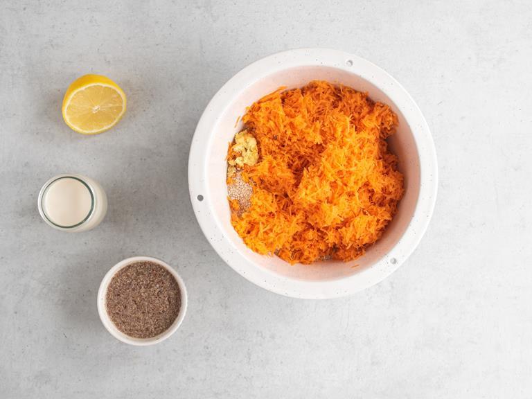 Starta marchewka z imbirem w misce. Obok napęczniałe siemie lniane, połówka cytryny i mleko migdałowe.