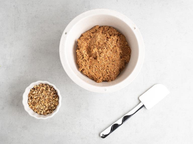 Posiekane orzechy włoskie w miseczce. Obok wymieszane składniki na ciasto  marchewkowe.