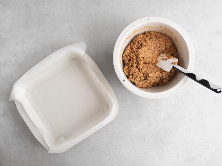 Foremka o wymiarach 21 x 21 cm wyłożona papierem do pieczenia. Obok w misce wymieszane ciasto marchewkowe.
