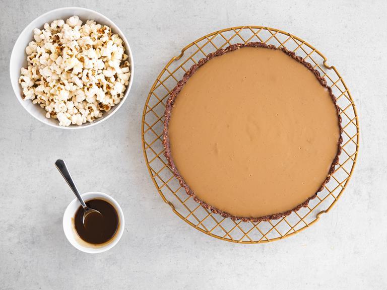 Tarta z kremem wegański słony karmel. Obok w miskach: karmel i popcorn.
