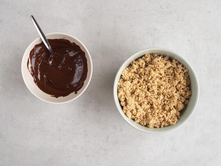 Rozpuszczona czekolada i pozostałe wymieszane składniki na spód ciasta w misce.