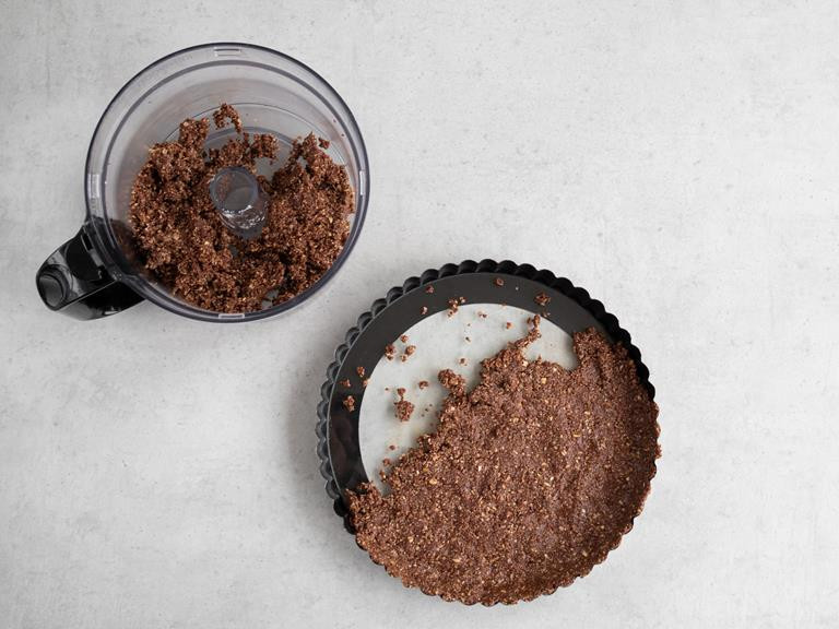 Wymieszany spód ciasta nakładany do formy na tartę.