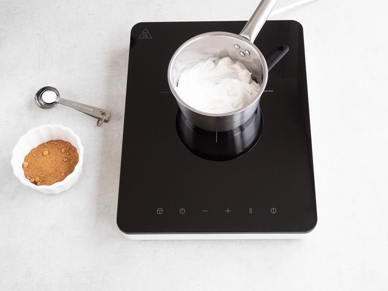Śmietanka kokosowa w garnku oraz sól i cukier kokosowy w miseczce.