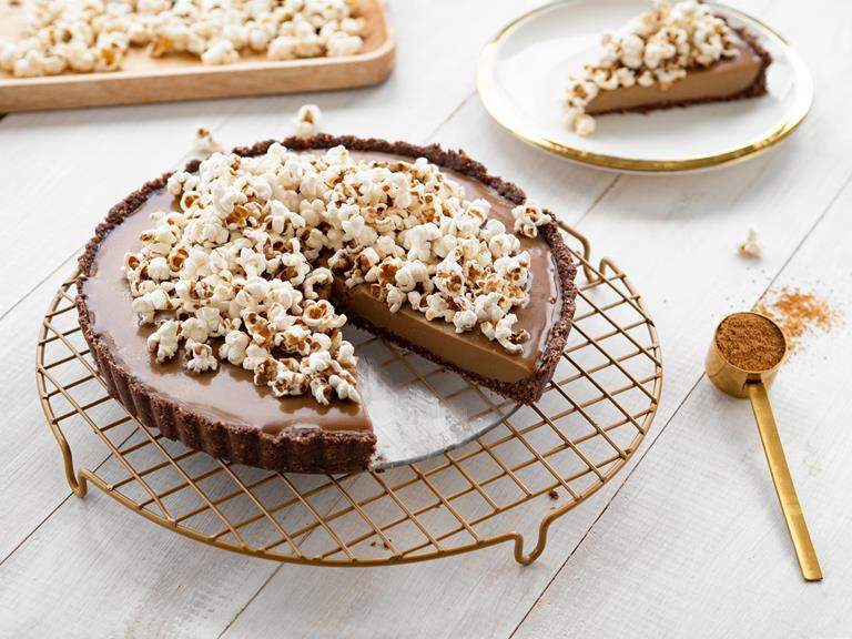 Wegańska tarta słony karmel z popcornem na białym blacie ze złotymi dodatkami.