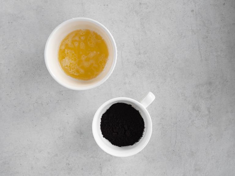 Czarne kakao w miseczce i rozpuszczone masło.