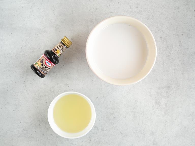 Mleko migdałowe i olej w miseczkach. Obok ekstrakt waniliowy.