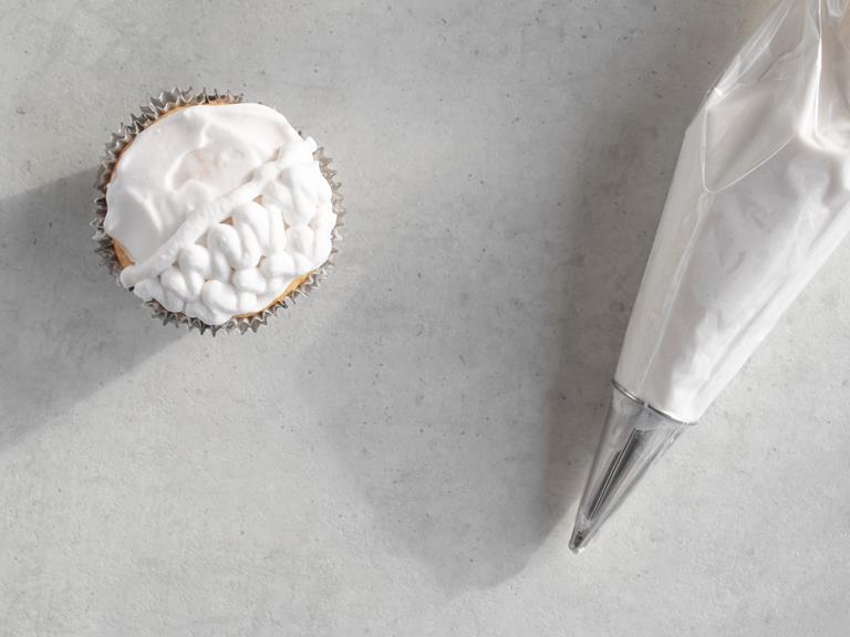 Babeczka z kremem kokosowym w kształcie mózgu i rękaw cukierniczy.