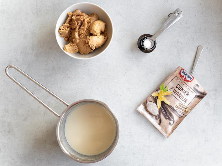 Masło orzechowe w misce, cukier z wanilią oraz rozpuszczona biała czekolada z olejem kokosowym.