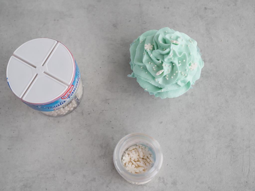 babeczka z niebieskim kremem, posypki śnieżynki i cukrowe dekoracje