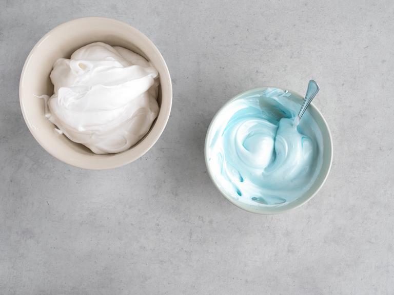 Biała masa bezowa i niebieska masa bezowa w osobnych miseczkach.