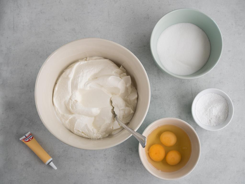 w misce twaróg obok w trzy jajka wybite w miseczce cukier oraz mąka