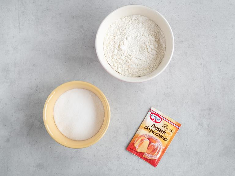 Mąka pszenna i cukier w miseczkach i proszek do pieczenia.