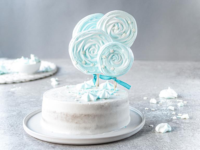 Wegański tort zimowy bez laktozy z lizakami bezowymi na białej paterze.