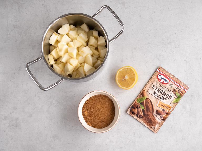 Obrane jabłka w garnku. Połowa cytryny. Cukier kokosowy w miseczce i cynamon mielony.