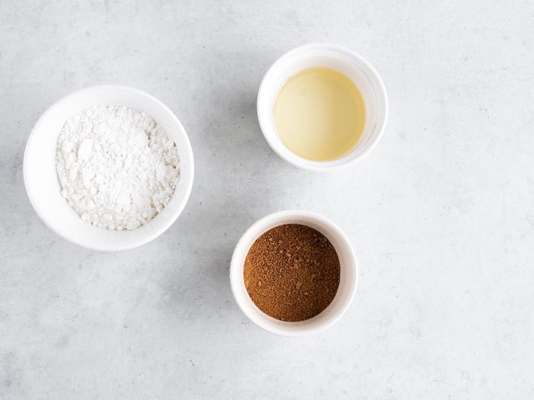 Mąka ryżowa, cukier kokosowy i rozpuszczony olej kokosowy w miseczkach.