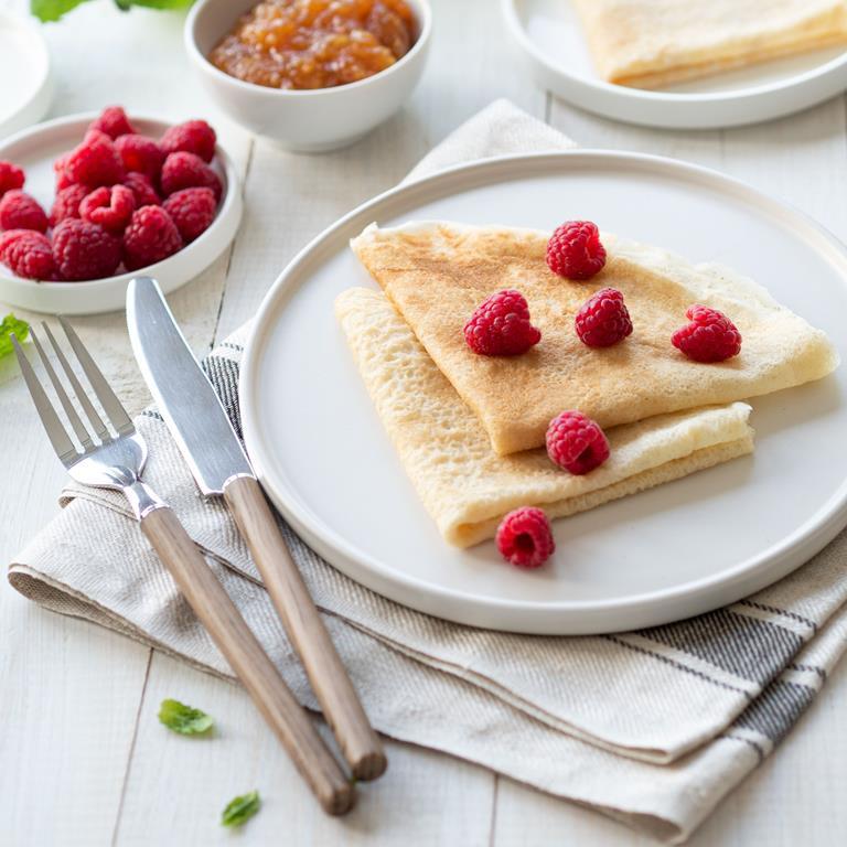 Naleśniki wegańskie na bialym talerzu z malinami