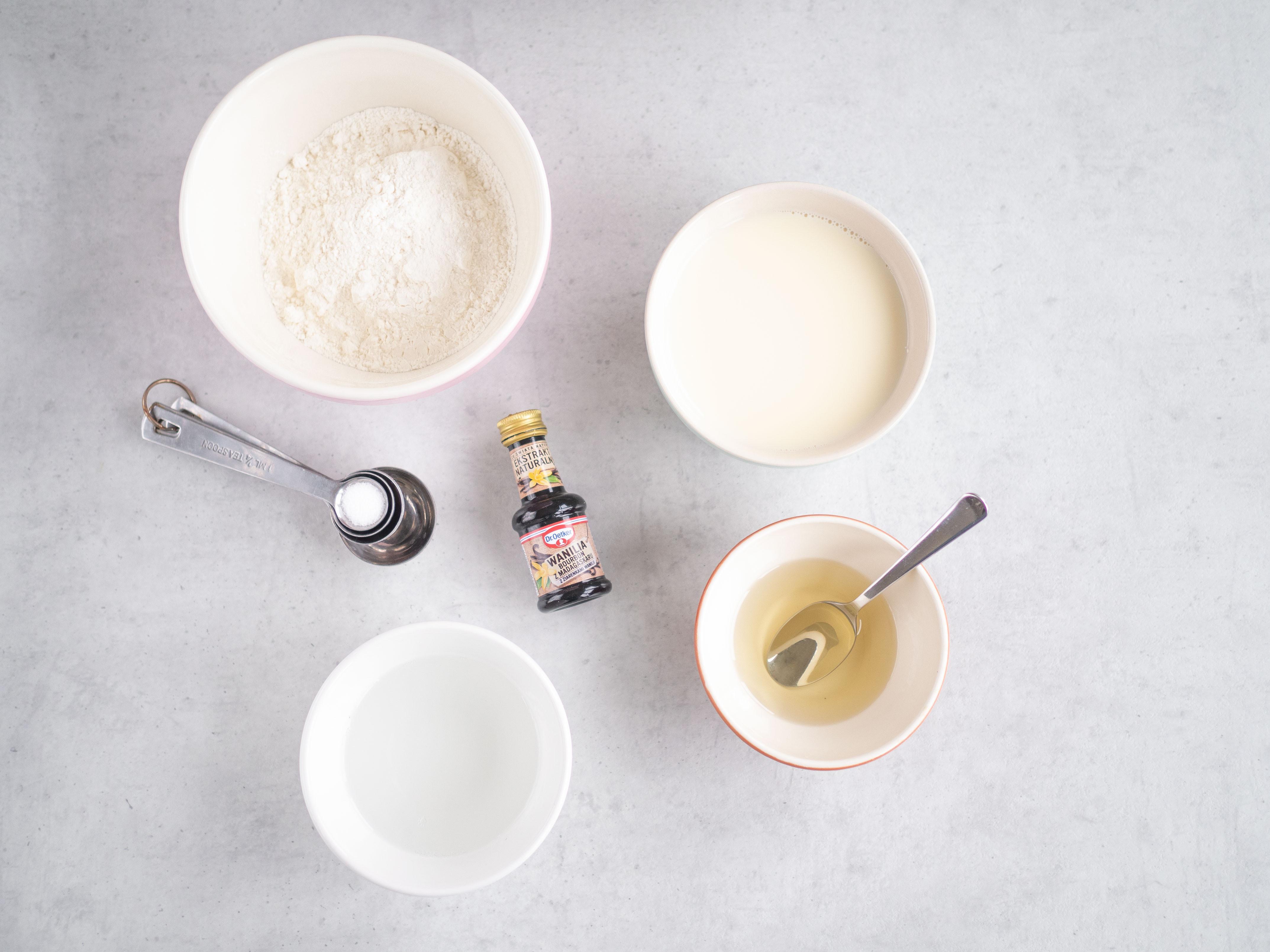 Olej kokosowy, mąka pszenna, sól, mleko sojowe i woda w osobnych miseczkach. Obok ekstrakt waniliowy.