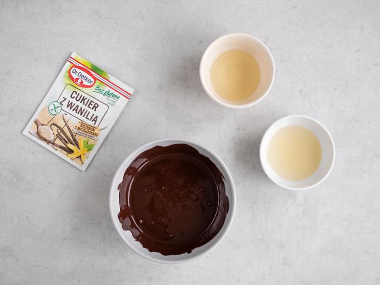 Cukier z wanilią bez glutenu. Rozpuszczona czekolada oraz syrop z agawy i olej kokosowy w miseczkach.