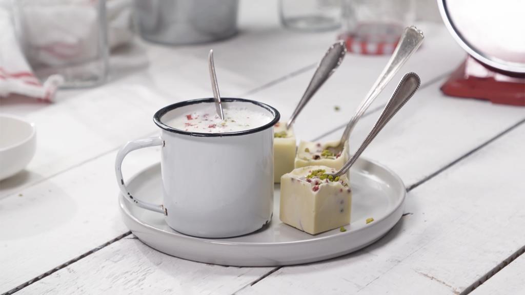 Biała. rozpuszczona czekolada na łyżeczce z różowym pieprzem i pokruszonymi pistacjami.