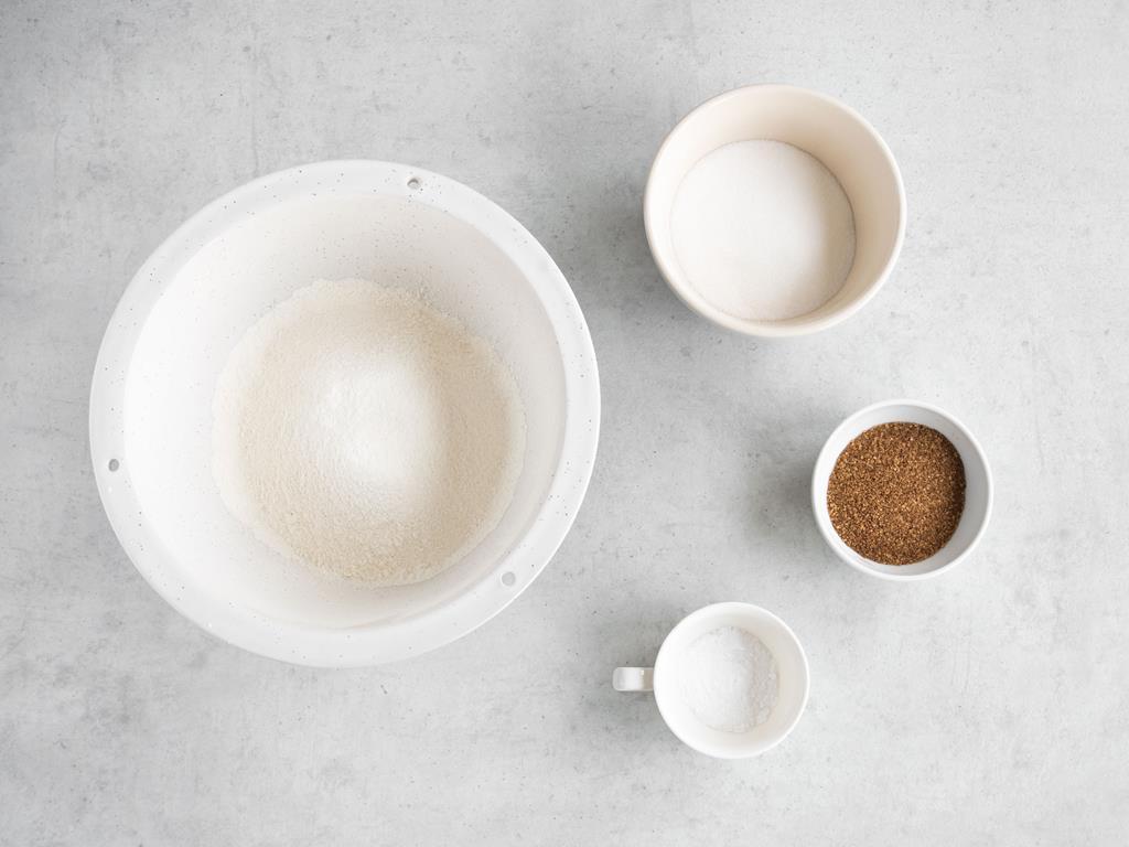 Mąka pszenna, cukier, soda i przyprawa korzenna w miseczkach.