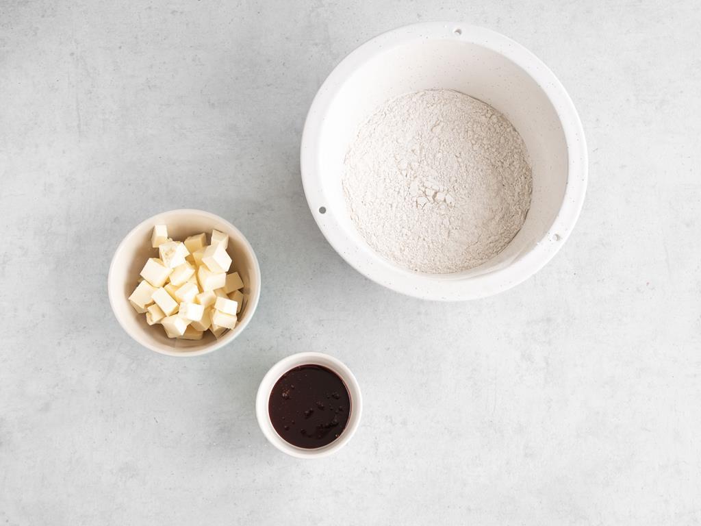 Masło roślinne pokrojone w kostkę. Mąka wymieszana z przyprawą korzenną i syrop z agawy w miseczce.