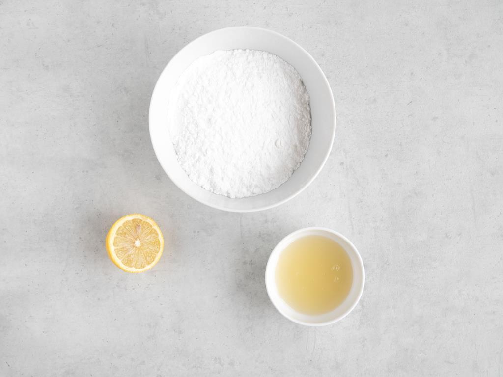 Aquafaba i cukier puder w miseczce. Obok połówka cytryny.