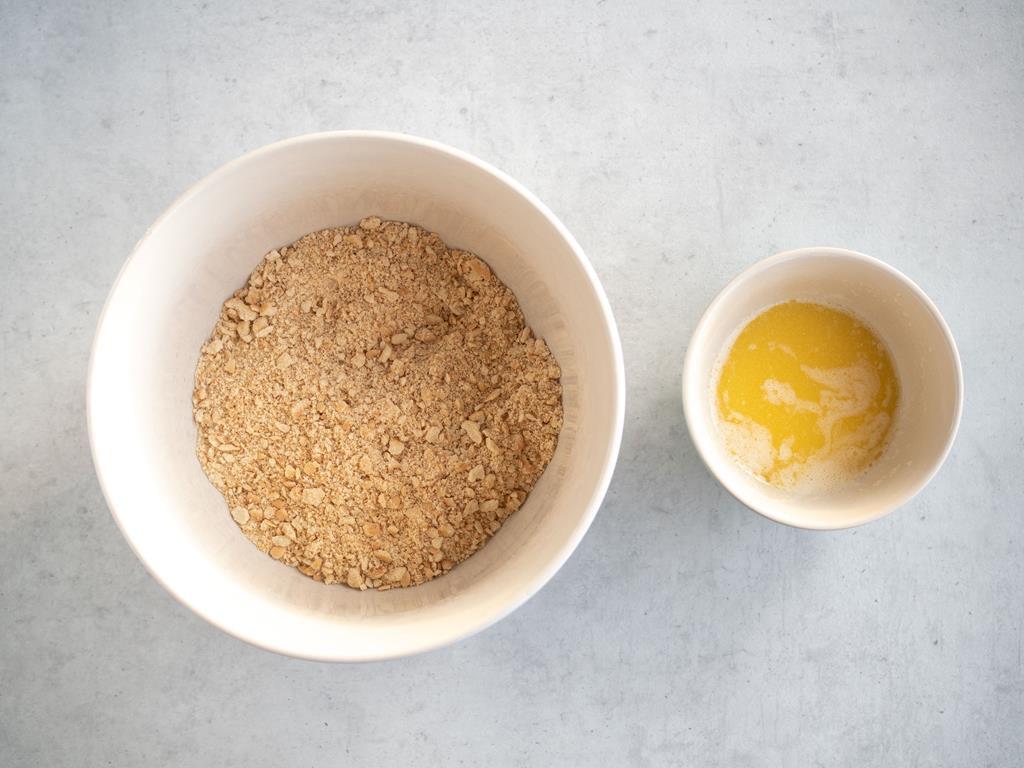 w misce pokruszone herbatniki obok w miseczce rozpuszczone masło