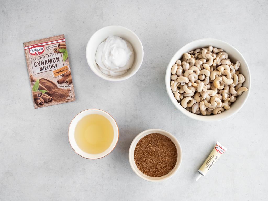 Nerkowce, mleko migdałowe, olej kokosowy i cukier kokosowy w miseczkach, Obok cynamon mielony i pasta z wanilii.