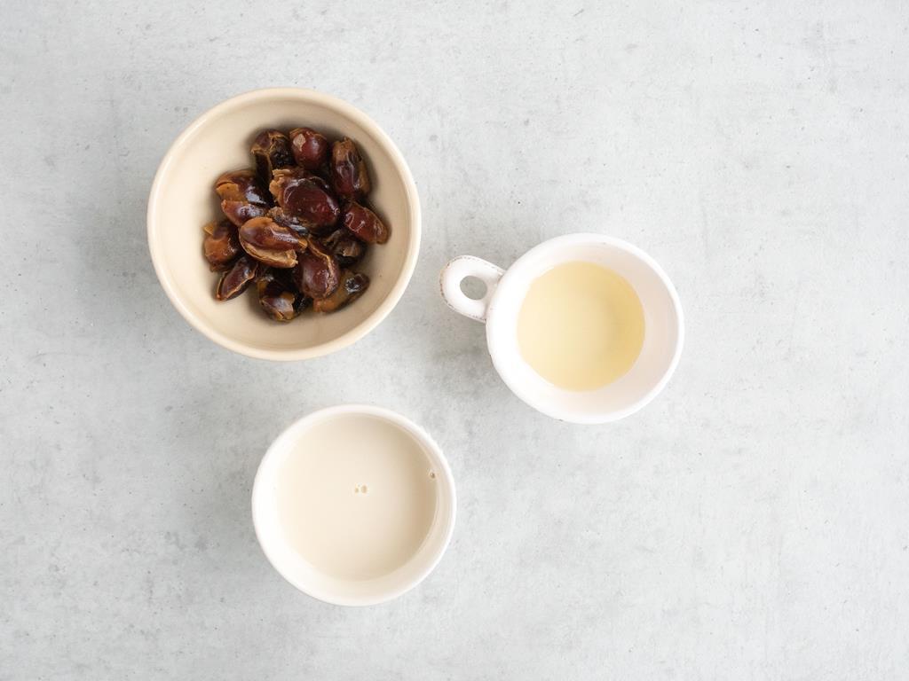 Odsączone daktyle, mleko migdałowe i olej kokosowy w miseczkach.