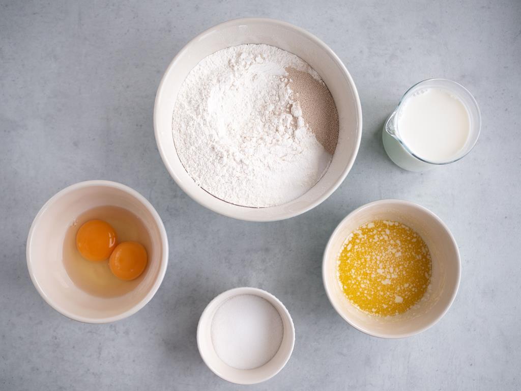 w miskach mąka z suszonymi drożdżami, roztopione masło, cukier oraz jajka