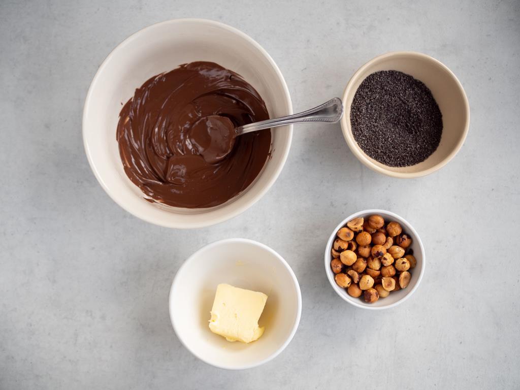 w miseczkach czekolada, mak, uprażone orzechy laskowe oraz masło