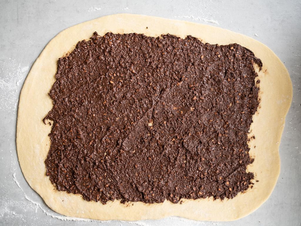 na stole rozwałkowane ciasto drożdżowe posmarowane nadzieniem czekoladowym